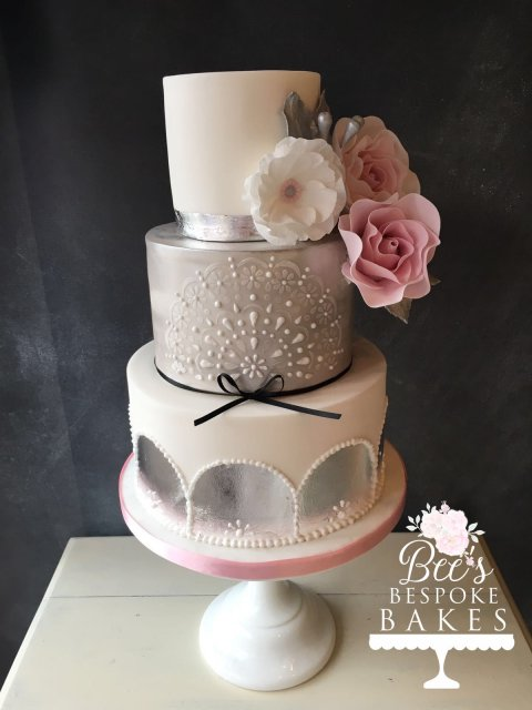 Gorgeous modern three tier wedding cake with silver leaf detail, sugar flowers, stencilling and lustre