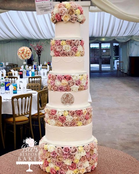 Towering ivory floral four tier wedding cake with hand piping and personalised monogram plaque.