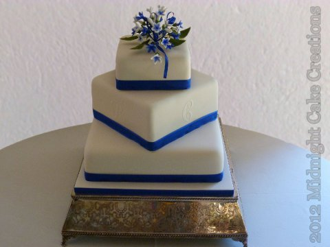 Blue and white offset square cake with stencilled personal monograms and blue sugar flower posy in the top. - Midnight Cake Creations