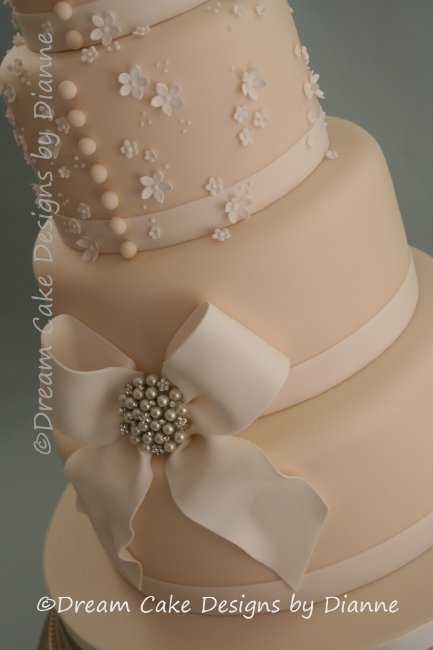 4 Tier Ivory Wedding Cake with sugar bow, delicate blossoms and diamante and pearl brooch - Dream Cake Designs (Dianne Stanley)