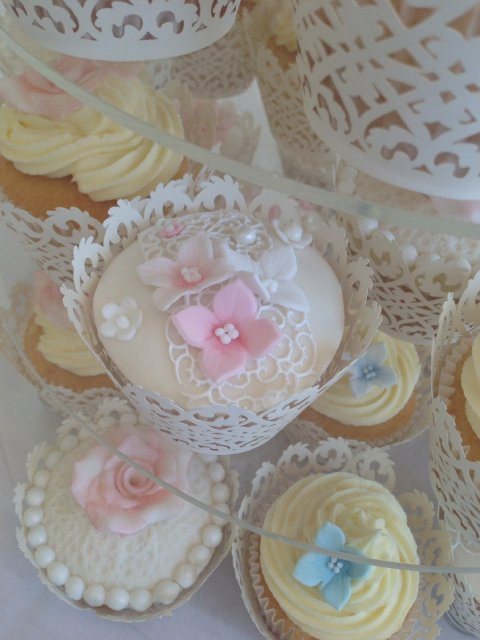 Cupcakes in lace wraps decorated with edible lace and sugar flowers