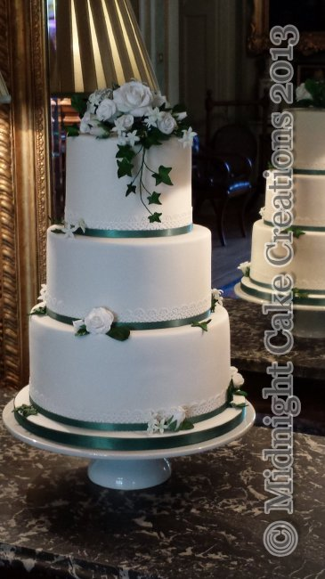 Elegant white cake with roses and foliage for a winter wedding. - Midnight Cake Creations