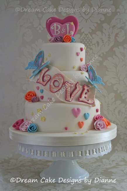3 tier 'LOVE' Wedding Cake decorated with butterflies, hearts and rolled ribbon roses with a love heart monogram cake topper - Dream Cake Designs (Dianne Stanley)