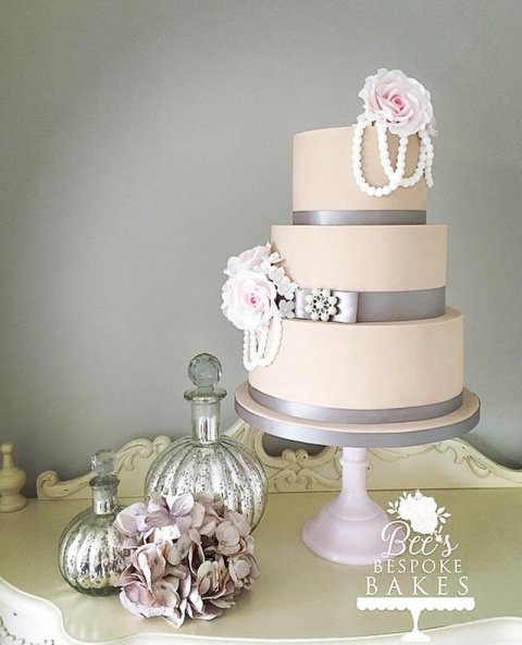 An elegant three tier latte wedding cake adorned with pearls and delicate pink sugar roses