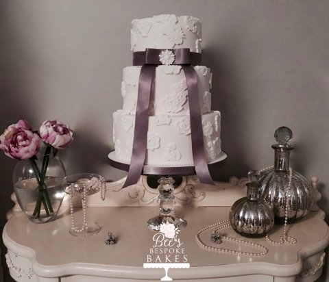 Graceful three tier wedding cake decorated with edible applique lace, grey ribbon and an edible brooch
