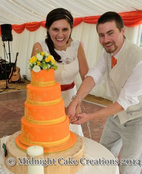 Beautiful, striking orange cake with gold royal icing detail. - Midnight Cake Creations