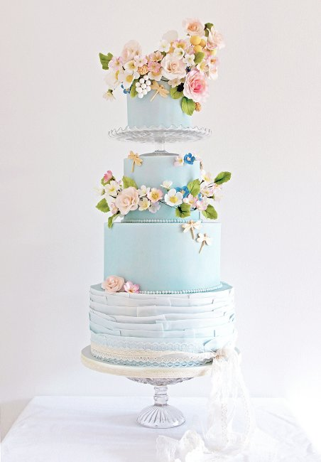 Bohemian Romance, a crown of sugar flowers on this pale blue and ruffle wedding cake. - Cobi & Coco Cakes