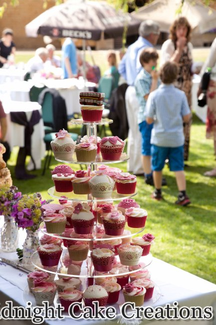 Cupcake tower with a variety of coordinating toppers and details for a picnic themed wedding. - Midnight Cake Creations