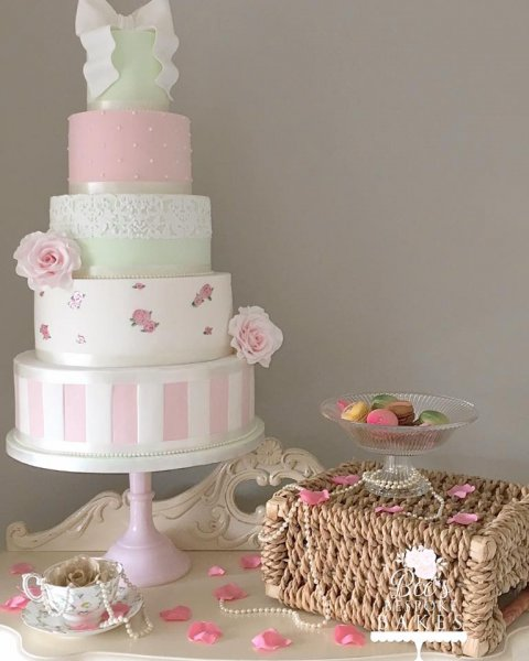 Vintage inspired four tier wedding cake with delicate hand painted roses, candy stripes, cake lace, sugar roses and a beautiful sugar bow