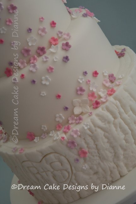 4 Tier White Wedding Cake with pink lovebirds and shades of pink and purple blossoms finished with a log style lower tier with carved heart and initials - Dream Cake Designs (Dianne Stanley)