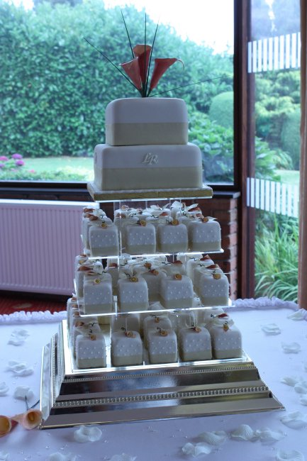 Two tiered wedding cake with Individually iced cakes decorated with sugar calla lilies